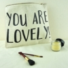 make up bag with you are lovely on the front with makeup