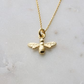 gold plated bee necklace on white marble