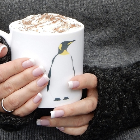 large bone china penguin mug with a penguin on it held in hands wearing mittens