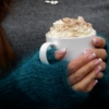 bone china mug with cream and held in hands wearing mohair mittens