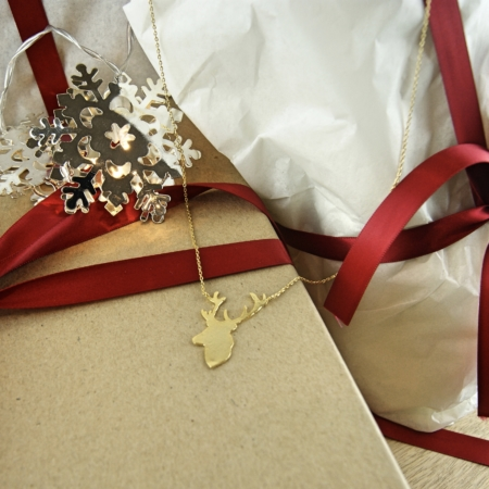 gold plated stag necklace on a gift box with snowflake lights
