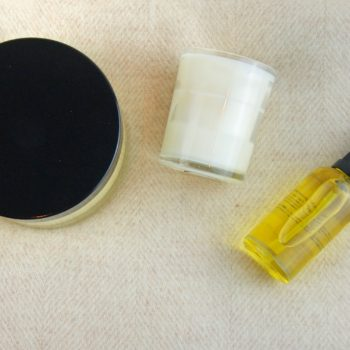 face oil body balm and a candle on wool blanket home of juniper