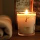 lit candle with happy on front in gold type near cosy lantern and home of juniper blanket