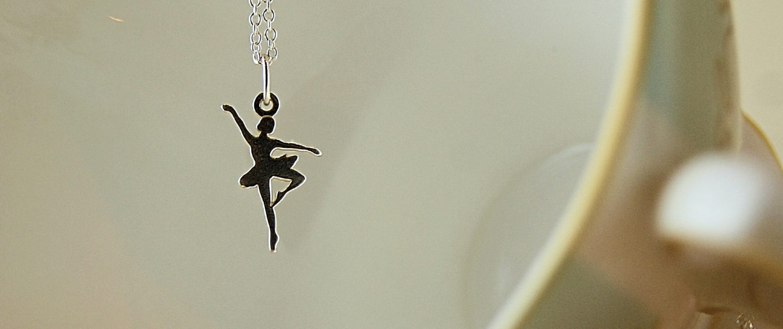 ballerina necklace hanging over tea cup