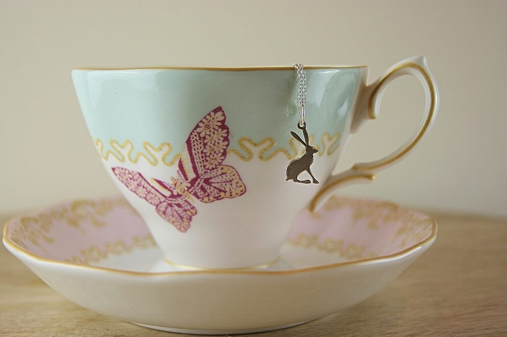 Cup and saucer with hare necklace on it