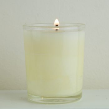 cream candle in glass votive burning - home of juniper