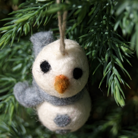 felt snowman in grey scarf hanging in tree