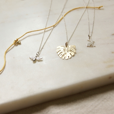 bee wish bracelet next to silver bee necklace brass monstera necklace silver hare necklace